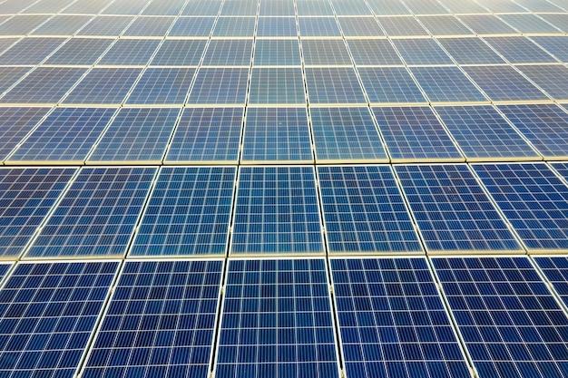 Zbliżenie powierzchni niebieskich fotowoltaicznych paneli słonecznych zamontowanych na dachu budynku do produkcji czystej ekologicznej energii elektrycznej. produkcja koncepcji energii odnawialnej.