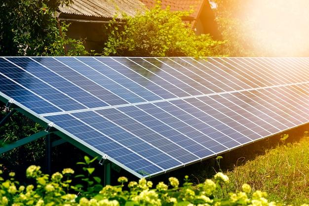 Zbliżenie powierzchni oświetlonego słońcem nowoczesnego, oszczędnego, wydajnego, samodzielnego, niebieskiego, błyszczącego słonecznego systemu paneli fotowoltaicznych wytwarzających odnawialną czystą energię na zielonej trawie i liściach drzew.