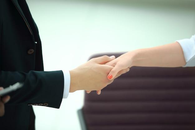 Zbliżenie .powitalny uścisk dłoni biznesmena i kobiety biznesu na tle biura