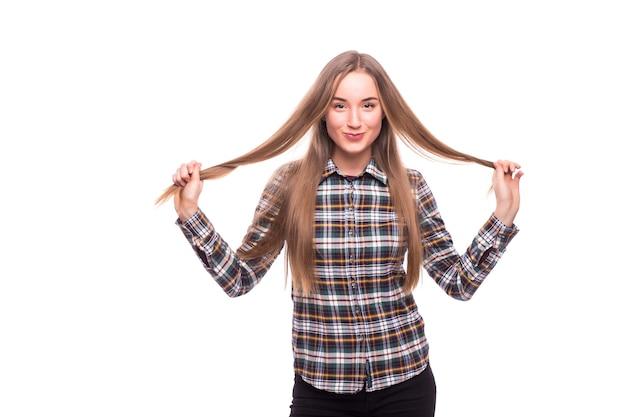 Zbliżenie pozytywna młoda kobieta dotyka jej włosów na białym tle na białej ścianie