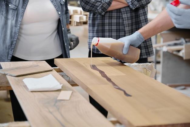 Zbliżenie pracownik ręka w ochronnych rękawiczkach z wykończeniową ochronną pokrywą dla drewna
