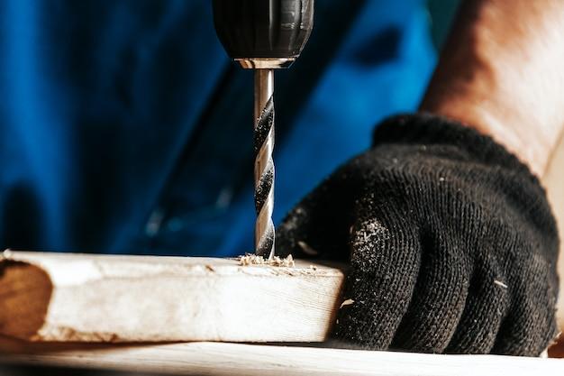 Zbliżenie: pracownik śrubokręt z czarnym nowoczesnym śrubokrętem w warsztacie