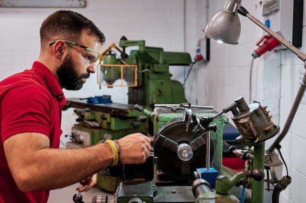 Zbliżenie pracownik w mundurowych i ochronnych szkłach pracuje na ostrzeniu obrabiarek narzędzie
