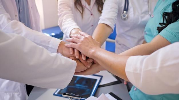 Zbliżenie pracowników medycznych układają ręce na stole razem dla wsparcia w pracy. zespół lekarzy w modern hospital. duch zespołowy w modern at clinic.