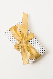 Zbliżenie: prezent zawinięty w kropkowany papier ozdobiony złotą wstążką na białym tle w tle