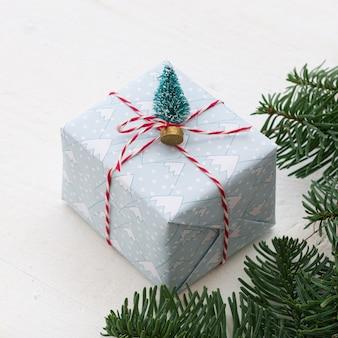 Zbliżenie prezentu na boże narodzenie lub nowy rok ozdobiony małą ozdobną choinką