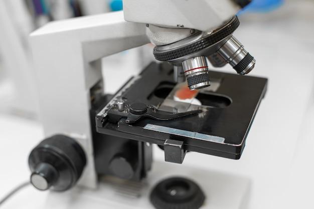 Zbliżenie próbki krwi na szkle w mikroskopie.