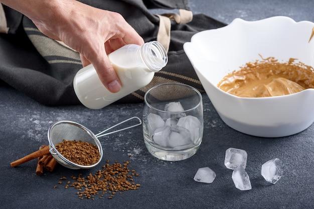 Zbliżenie proces robienia kawy dalgona, koreański napój na szarym stole w kuchni, ręka nalewa mleko do szklanki z lodem