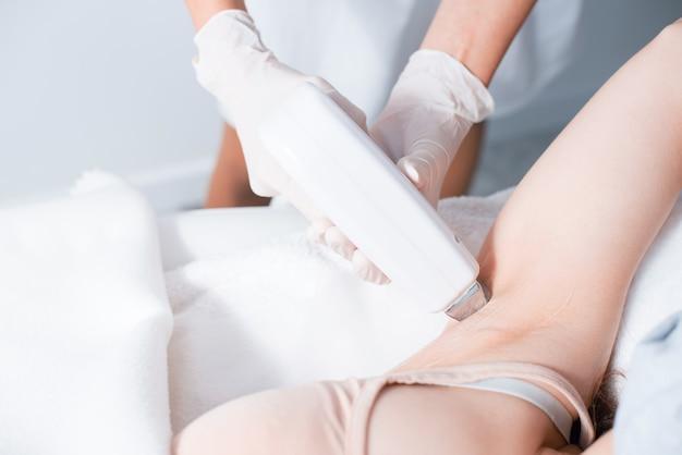 Zbliżenie procesu depilacji laserowej w salonie kosmetycznym. część pod pachami