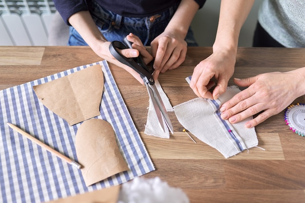 Zbliżenie procesu szycia. ręce kobiety i córki nastolatka dziecko do szycia zabawka lalka ubrania, nożyczki, szablony, igła, wzór, tkanina, maszyna do szycia