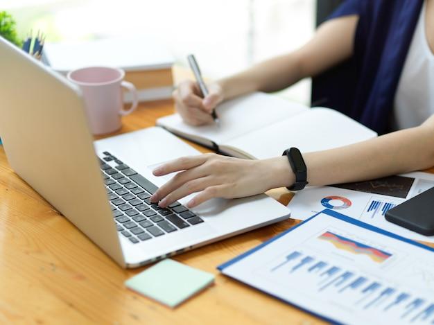 Zbliżenie profesjonalna kobieta pracująca w biurze, pracująca na laptopie i robiąca notatki, analizująca biznes
