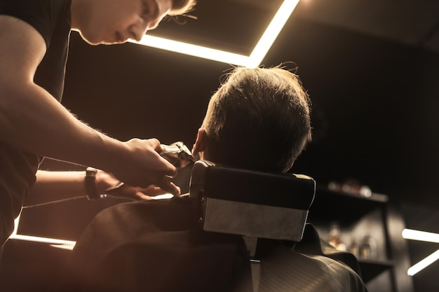 Zbliżenie profesjonalnego fryzjera, który czesuje brodę swojej młodej klientki, która podczas zabiegu patrzy w lustro.