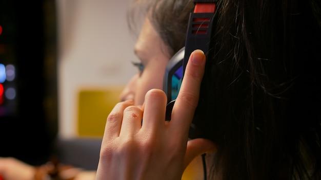 Zbliżenie profesjonalnego gracza noszącego zestaw słuchawkowy i rozmawiającego z innymi graczami do mikrofonu podczas turnieju e-sportowego. gracz siedzący na fotelu do gier grający w kosmiczną strzelankę za pomocą sprzętu rgb rgb