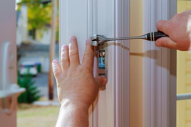 Zbliżenie profesjonalnego ślusarza instalowanie lub naprawianie nowego zamka deadbolt