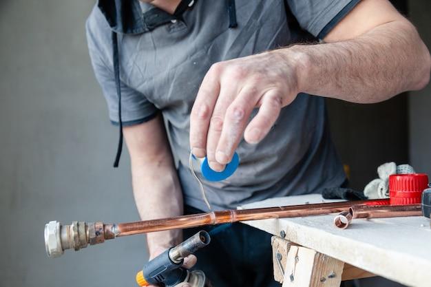 Zbliżenie profesjonalny mistrz hydraulik trzymając pastę topnikową do lutowania i lutowania szwów palnika gazowego z rur miedzianych.