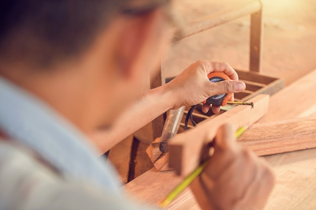 Zbliżenie profesjonalny stolarz trzymający miarkę i ołówek podczas pomiaru deski w warsztacie stolarskim.styl vintage
