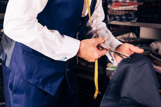 Zbliżenie projektant mody cięcia tkaniny nożyczkami