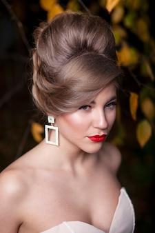 Zbliżenie przedni portret pięknej narzeczonej portret ślubny makijaż fryzura, wspaniała młoda kobieta w białej sukni poza. widok pionowy.