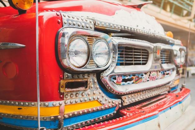 Zbliżenie przednich świateł i kratki silnika starych czerwonych ciężarówek