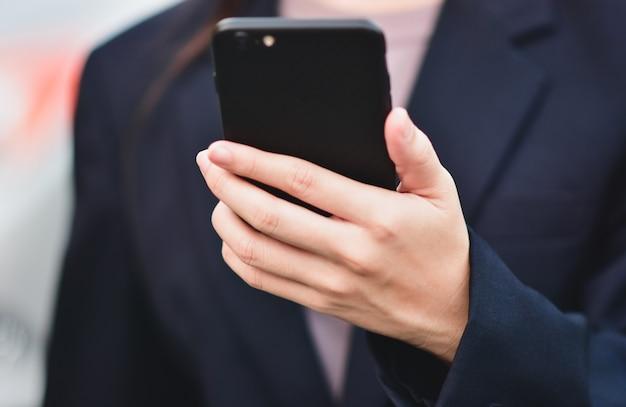 Zbliżenie przedsiębiorców korzystających z telefonu na smartfonie