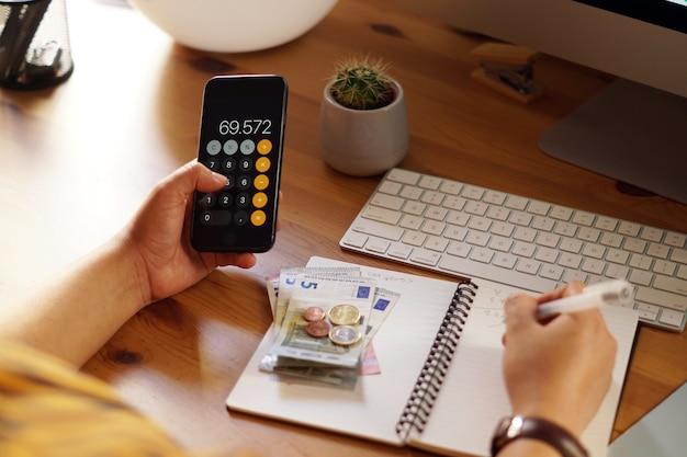 Zbliżenie przedsiębiorcy pracującego w domu nad swoimi finansami osobistymi i oszczędnościami