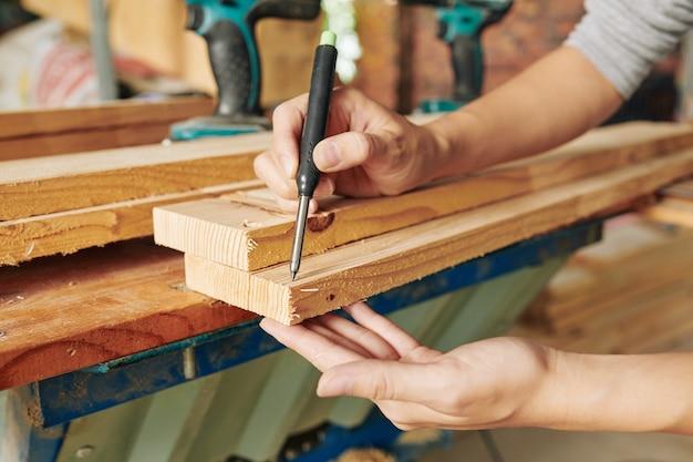 Zbliżenie przedstawia stolarza rysującego ślady na długiej drewnianej desce przed jej cięciem i wykonaniem mebla