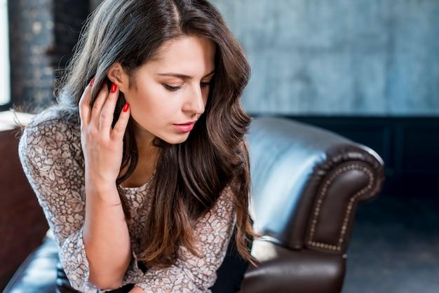Zbliżenie: przemyślany piękna młoda kobieta siedzi na kanapie