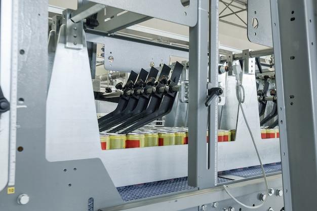Zbliżenie przenośnika taśmowego w ruchu podczas produkcji i butelkowania napojów w puszkach