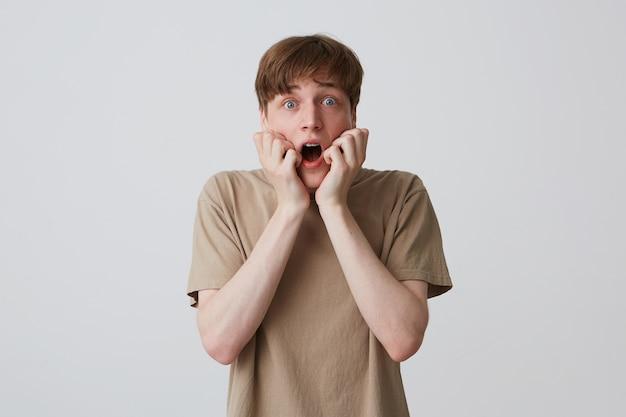 Zbliżenie przerażony zszokowany młody człowiek w beżowej koszulce z krótką fryzurą