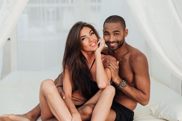 Zbliżenie przetargu kochająca młoda para siedzi na białym łóżku