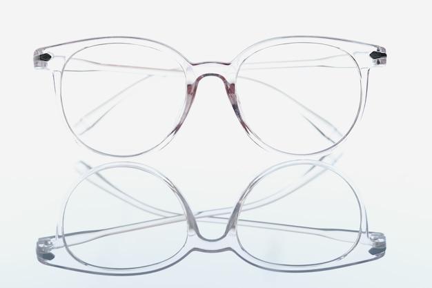 Zbliżenie przezroczystych okularów do widzenia na białym tle z lustrzanym odbiciem