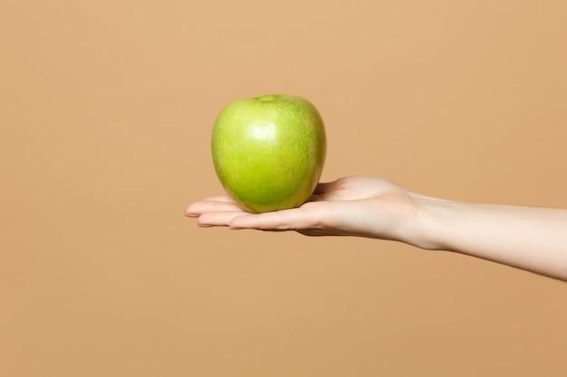 Zbliżenie przycięte kobiet trzyma w ręku świeże dojrzałe zielone jabłko na białym tle na beżowej pastelowej ścianie