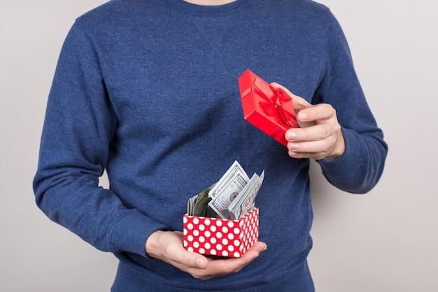 Zbliżenie przycięte zdjęcie zadowolonego pomyślnego faceta szczęścia otwierającego mały czerwony mały pakiet pełen pieniędzy na białym tle szarym tle