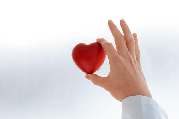Zbliżenie. przycięty obraz lekarza przedstawiający małe czerwone serce. pojęcie ochrony zdrowia.