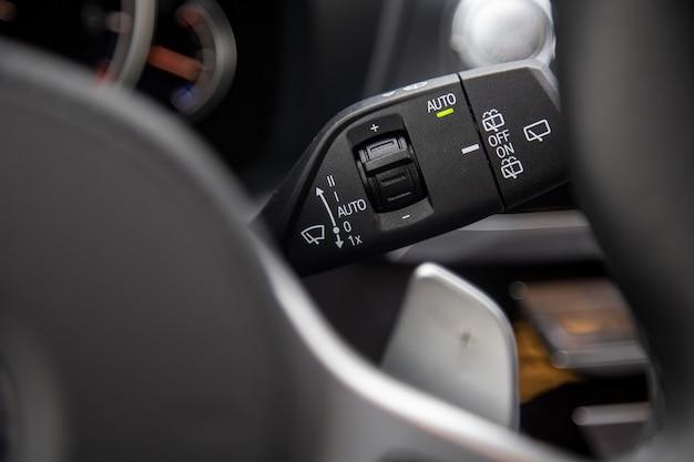 Zbliżenie przycisków wielofunkcyjnej dźwigni kierunkowskazów z przyciskami sterowania wycieraczkami w nowoczesnym samochodzie