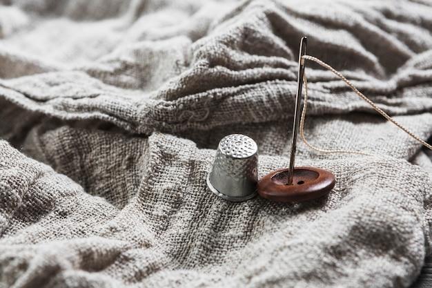 Zbliżenie przycisku; naparstek; igła i nić na tkaninie jutowej