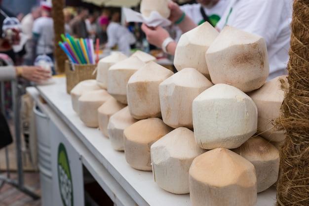 Zbliżenie przygotowanych łuskanych orzechów kokosowych na wózku z napojami na imprezie busy food festival