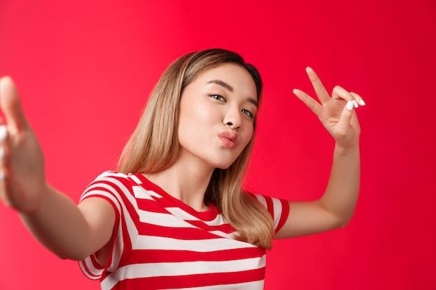 Zbliżenie przyjacielskie wychodzące słodkie azjatyckie dziewczyny blond fryzury robiące zdjęcie trzymaj smartfon złóż wargi...
