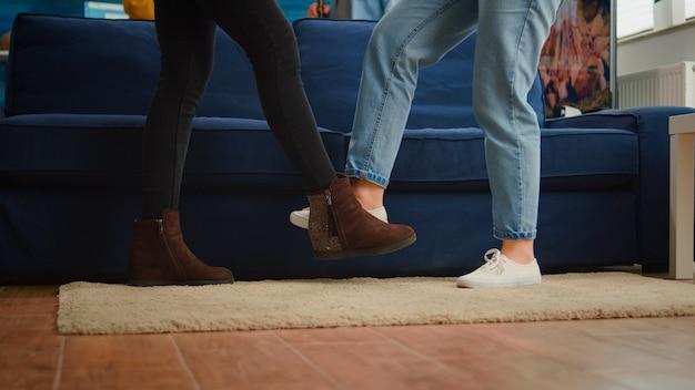 Zbliżenie przyjaciół dotykających stóp, zachowujących dystans społeczny, witając się, zapobiegając rozprzestrzenianiu się koronawirusa. ludzie w tle trzymający butelki po piwie organizujący imprezę w salonie podczas covid19