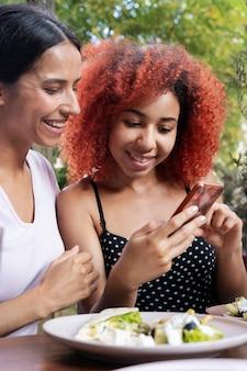 Zbliżenie przyjaciół patrzących na telefon