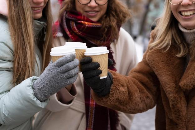 Zbliżenie przyjaciół trzymając filiżanki kawy