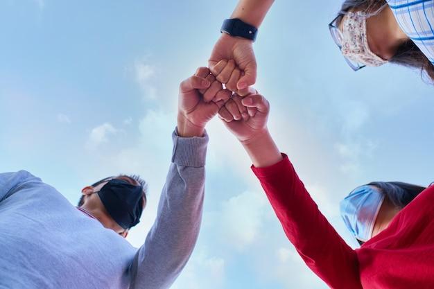Zbliżenie przyjaciół z ochronną maską na twarz robiąc fistbumping gest