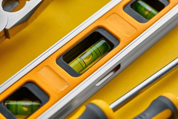 Zbliżenie przyrząd warsztatowy. narzędzia stolarskie, sprzęt budowlany lub stolarski, śrubokręt i pale, poziomica