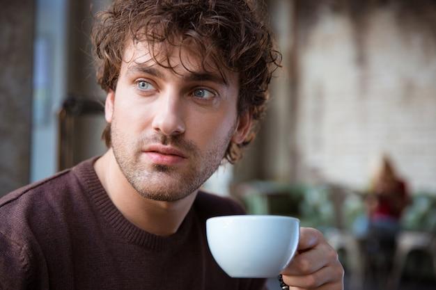 Zbliżenie przystojnego, atrakcyjnego, kontemplacyjnego, kręconego, męskiego picia kawy