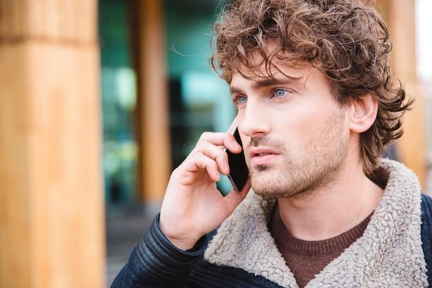 Zbliżenie przystojny atrakcyjny poważny skoncentrowany kędzierzawy młody mężczyzna rozmawia przez telefon komórkowy