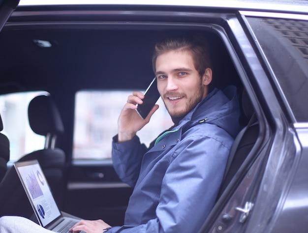 Zbliżenie przystojny biznesmen siedział w luksusowej limuzynie, pracując na komputerze przenośnym