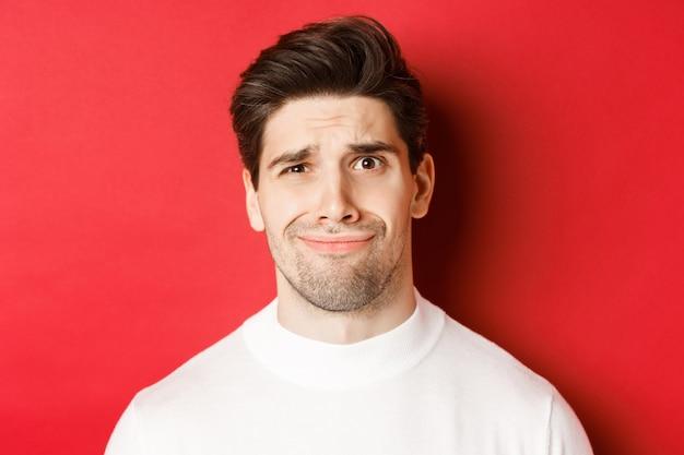 Zbliżenie: przystojny mężczyzna czuje się nieswojo, krzywiąc się i patrząc na coś nieprzyjemnego, stojąc na czerwonym tle