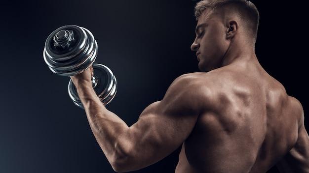 Zbliżenie przystojny mężczyzna mocny atletyczny kulturysta robi ćwiczenia z hantlami fitness muskularny ...