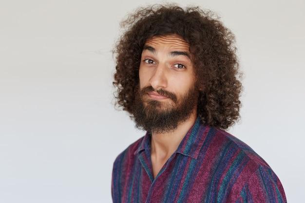 Zbliżenie: przystojny młody brodaty brązowooki mężczyzna z ciemnymi kręconymi włosami unoszącymi brwi i marszczącym czoło podczas patrzenia, odizolowany