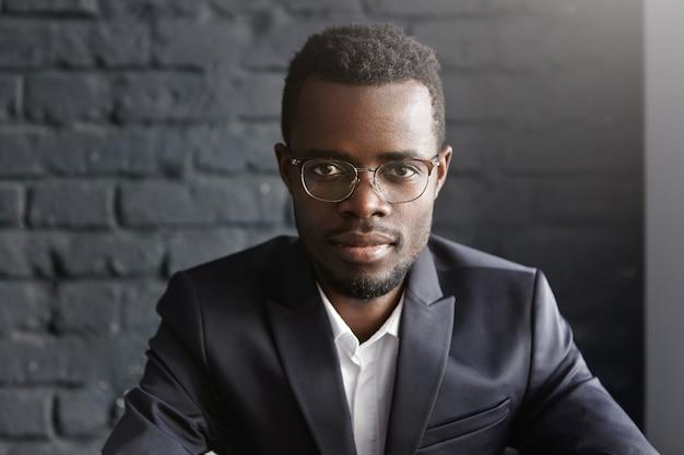 Zbliżenie przystojny młody ciemnoskóry przedsiębiorca w okularach i strojach wizytowych